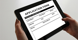hands holding an iPad with an application form on the screen