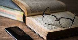 pair of glasses resting on an open book with a smartphone nearby